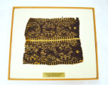 Coptic textile fragment of arm band from dress, brown wool and linen double band, animals and figures in a medallion